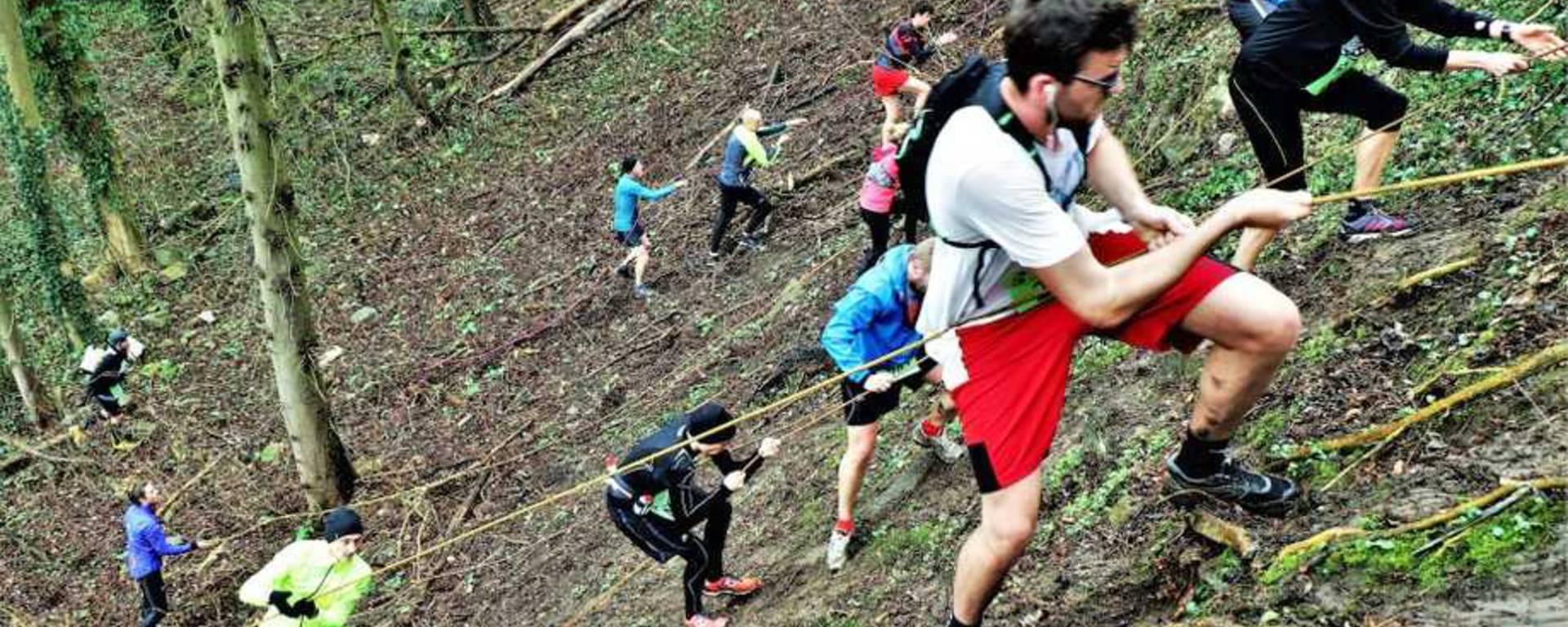 des traileurs escaladant une pente à l'aide de corde