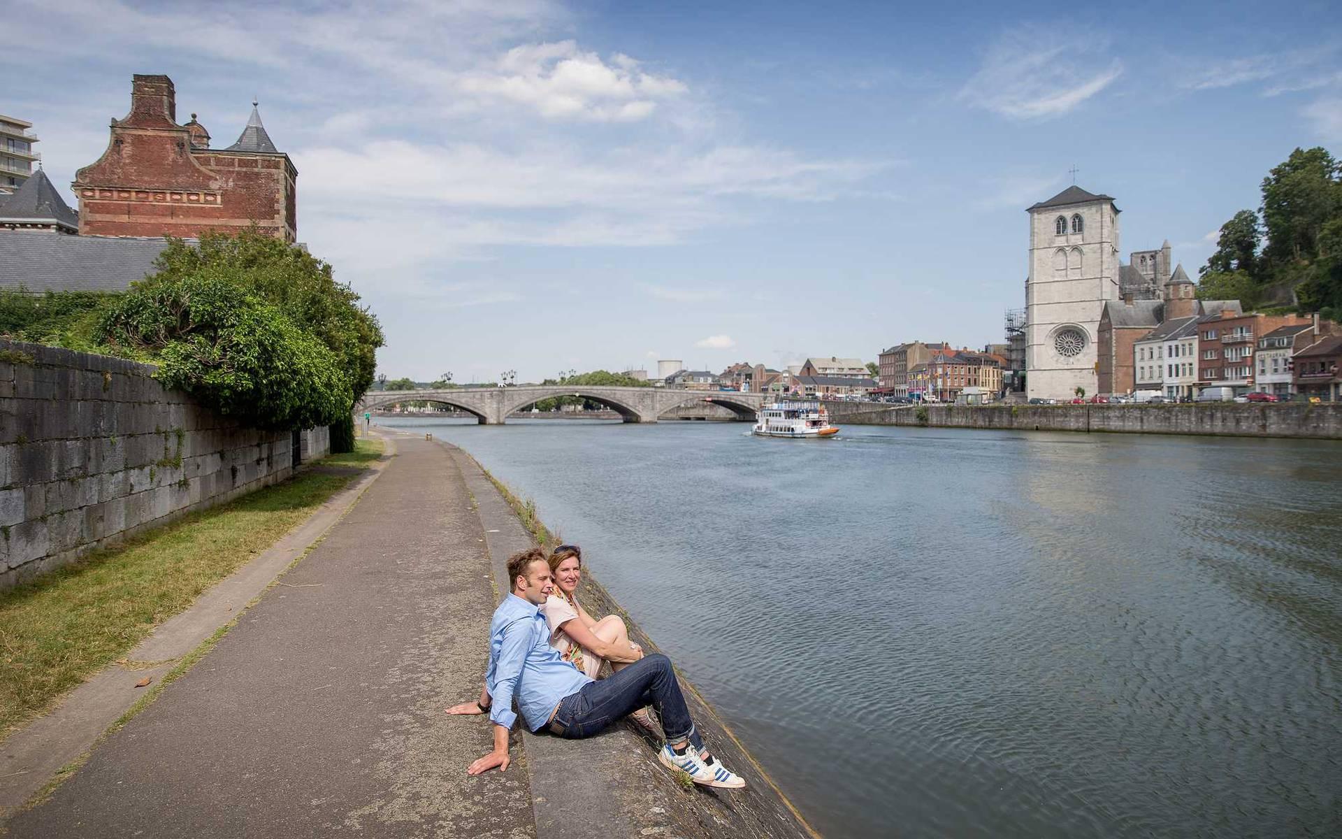 Un couple assis sur le bord de la Meuse